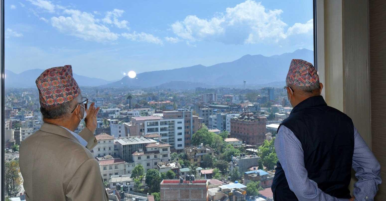 होटेलको झ्यालबाट धरहरा नियाल्दै ओली र नेपाल